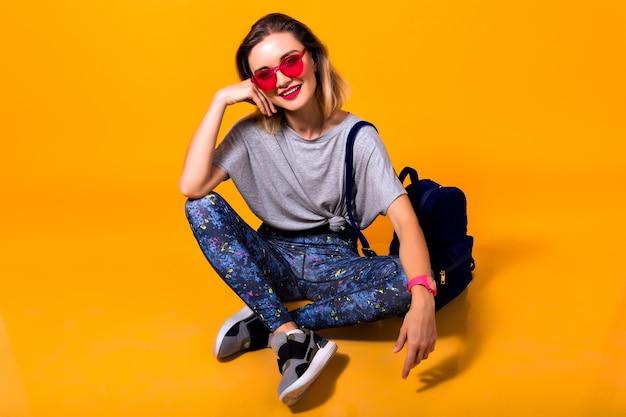 カラフルなレギンスとトレンディなシャツが床に座っている女の子の屋内写真。黄色の背景でポーズとバックパックを保持しているスポーツシューズのスタイリッシュな若い女性のスタジオポートレート。 無料写真