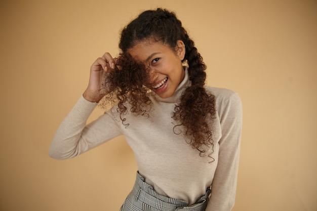 베이지 색 배경 위에 서서 좋은 분위기에 진심으로 웃고있는 동안 롤 넥 모직 스웨터를 입고 곱슬 꼰 머리를 가진 사랑스러운 젊은 어두운 피부 갈색 머리 아가씨의 실내 사진 무료 사진