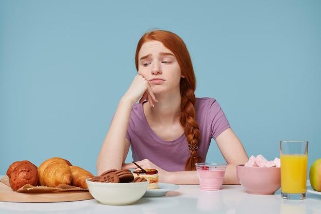 Фотография в помещении: рыжеволосая девушка с грустью смотрит на выпечку, думает о диете. Бесплатные Фотографии