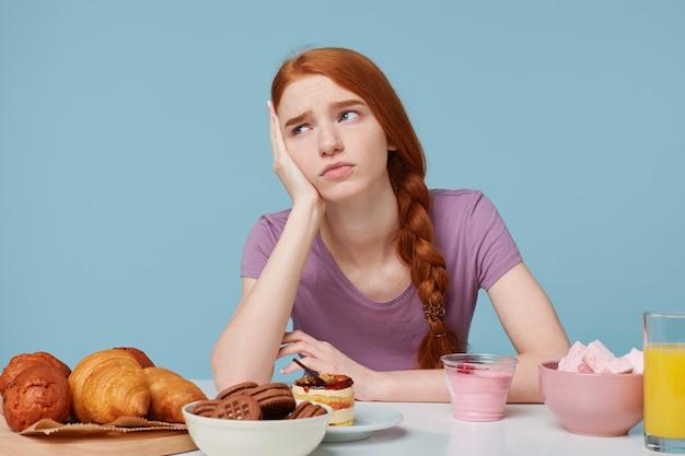食べ物、健康、食事、余分なカロリー、ベーキング製品、新鮮な果物について考えている悲しい赤毛の少女の屋内写真 無料写真