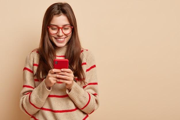 휴대 전화에 만족 한 10 대 소녀 텍스트의 실내 사진, 온라인에서 흥미로운 기사 읽기, 캐주얼 복장 착용, 여유 공간이있는 갈색 벽 위에 고립 된 자체 웹 페이지에 새로운 출판물 생성 무료 사진
