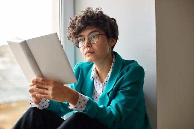 窓辺に座って注意深く興味深い本を読んで、中を見ながら彼女の茶色の目を驚かせて丸める眼鏡の若い魅力的な巻き毛のブルネットの女性の屋内写真 無料写真