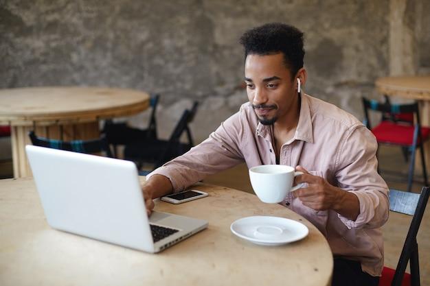 Foto al coperto di giovane maschio dalla pelle scura con la barba che lavora fuori ufficio, seduto a tavola su uno spazio di coworking e controlla la posta sul suo laptop, tenendo la tazza di caffè in mano alzata Foto Gratuite