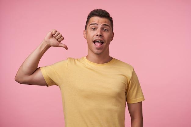 Foto interna del giovane ragazzo dai capelli castani con taglio di capelli corto che sfoglia su se stesso mentre guarda eccitatamente la fotocamera con la bocca aperta, in posa su sfondo rosa Foto Gratuite