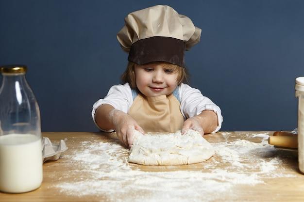 Immagine dell'interno della bella bambina europea allegra in copricapo da chef e grembiule che impasta la pasta al tavolo della cucina, facendo il pane o una torta. pasticceria, cucina, panetteria, cottura e preparazione del concetto Foto Gratuite