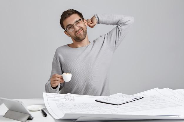 Immagine interna di designer creativo maschio oberato di lavoro, si allunga mentre si siede a tavola, Foto Gratuite