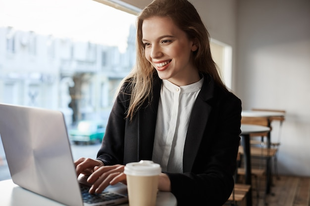 Indoor portrait of attractive european woman sitting in cafe, drinking coffee and typing in laptop, being happy and pleased. Free Photo