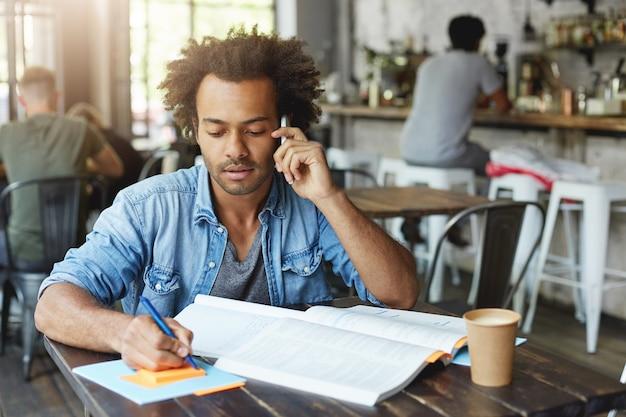 Ritratto dell'interno dello studente laureato universitario afroamericano alla moda attraente che parla sul telefono intelligente con il suo supervisore di ricerca mentre si lavora su carta del diploma, seduto al tavolo del bar Foto Gratuite