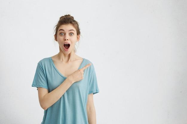 Ritratto dell'interno di bella donna con il nodo dei capelli che indossa la maglietta casuale con gli occhi saltati fuori e la bocca caduta che indica con il dito al copyspace Foto Gratuite