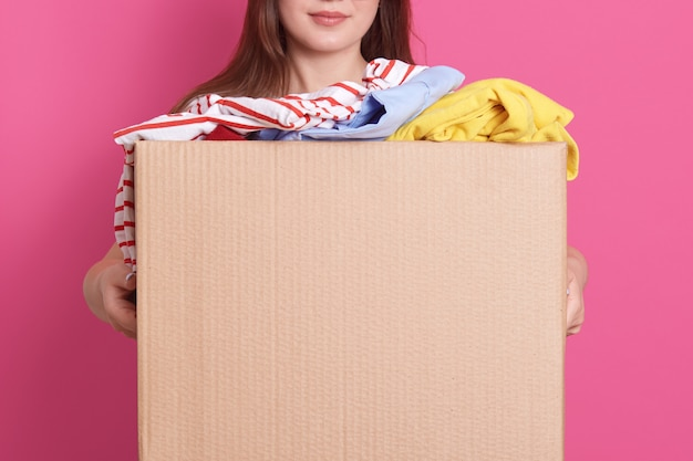 Indoor portrait of faceless girl standing with cardboard box in hands, holding carton box full of fashionable clothes isolated on rosy wall. donation, charity and volunteering concept. Free Photo