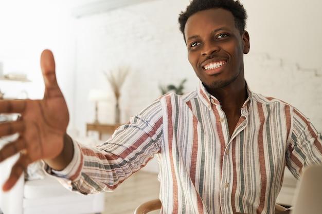 Ritratto dell'interno del giovane africano sicuro bello in camicia a strisce che ha espressione facciale amichevole Foto Gratuite