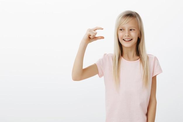 Ritratto dell'interno della ragazza adorabile felice soddisfatta con i capelli biondi, guardando la piccola cosa, modellandola con le dita Foto Gratuite