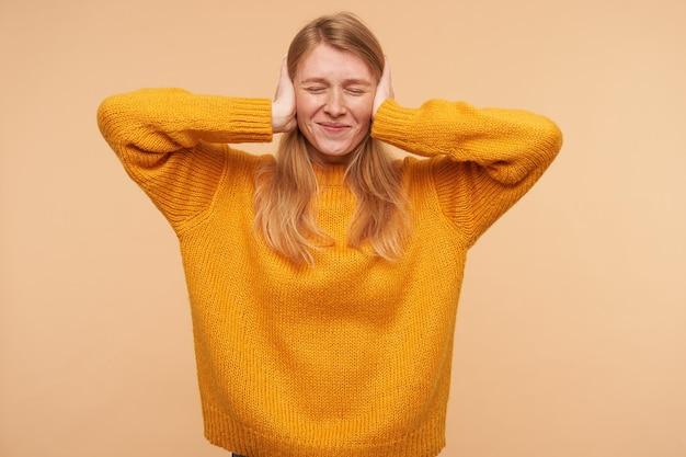 Ritratto dell'interno di bella giovane signora dai capelli lunghi con acconciatura casual sorridente leggermente con gli occhi chiusi e tenendo i palmi sollevati sulle orecchie, in posa sul beige Foto Gratuite