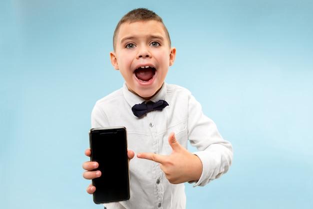 Крытый портрет привлекательного мальчика, держащего пустой смартфон Бесплатные Фотографии