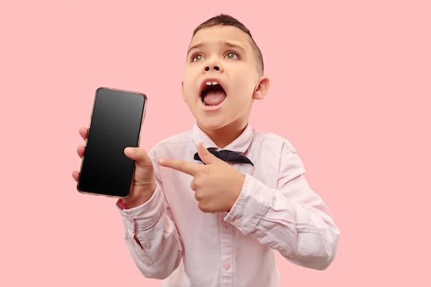 空白のスマートフォンを保持している魅力的な少年の屋内肖像画 無料写真
