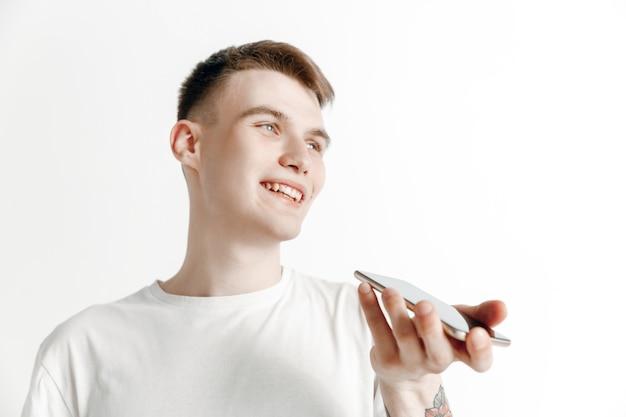 회색 배경에 고립 된 매력적인 젊은 남자의 실내 초상화, 스마트 폰을 들고, 음성 제어를 사용하여 행복하고 놀란 느낌. 인간의 감정, 표정 개념. 무료 사진