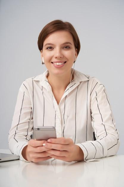 Крытый портрет красивой молодой кареглазой брюнетки, позитивно смотрящей с очаровательной улыбкой, сидящей на белом со смартфоном в руках Бесплатные Фотографии