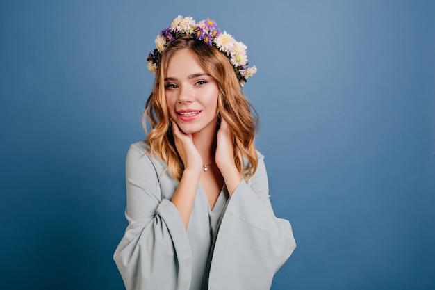 光沢のあるブロンドの髪を持つのんきな若い女性の屋内肖像画 無料写真