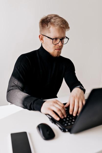 Крытый портрет европейского молодого человека в черном пуловере и очках, работающих с ноутбуком в светлом офисе в солнечный день. Бесплатные Фотографии
