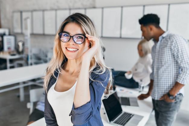 안경 및 회색 재킷에 흥분된 학생 여자의 실내 초상화. 사무실에서 포즈를 취하고 동료와 함께 웃고 매력적인 여성 직원. 무료 사진
