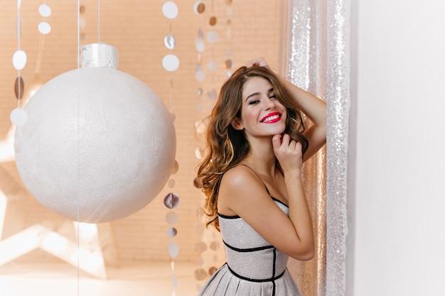 Крытый портрет великолепной женщины с праздничным, новогодним настроением в ярком стильном платье. кудрявая брюнетка широко улыбается Бесплатные Фотографии