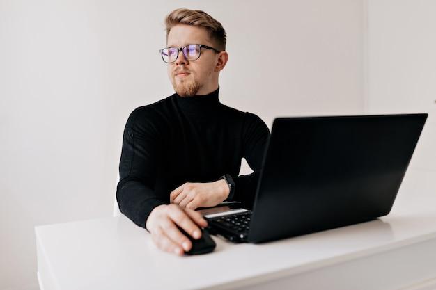 Крытый портрет красивого белокурого человека, работающего на ноутбуке в белом современном офисе. Бесплатные Фотографии