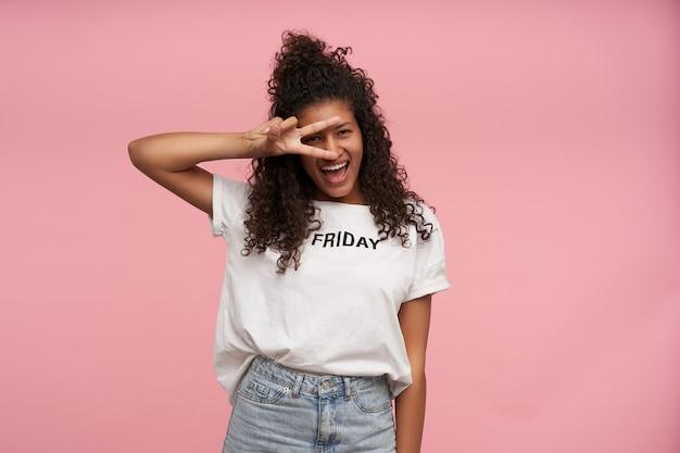 행복 한 젊은 갈색 머리 어두운 피부 여성의 실내 초상화 곱슬 긴 머리를 가진 흰색 티셔츠와 청바지 분홍색에 포즈, 그녀의 얼굴에 평화 제스처를 제기하고 즐겁게 웃고 무료 사진