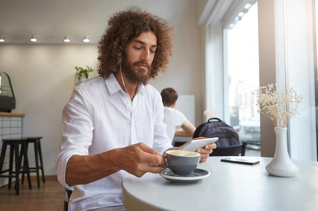 白いシャツを着て、タブレットでイヤホンで音楽を聴きながらコーヒーを飲みに行く素敵な巻き毛の暗い髪の男の屋内の肖像画 無料写真