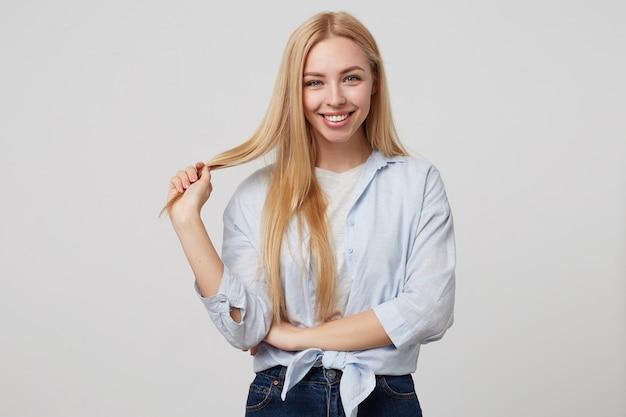 Крытый портрет красивой молодой блондинки, улыбающейся, держащей прядь волос, в повседневной одежде Бесплатные Фотографии