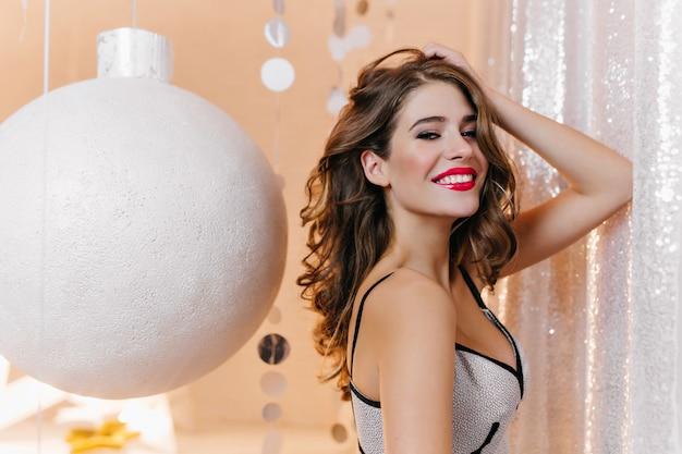 Крытый портрет стройной бледной девушки с красивой улыбкой, играющей с темными вьющимися волосами. очаровательная модная женщина в белом платье позирует на вечеринке с огромной рождественской игрушкой. Бесплатные Фотографии