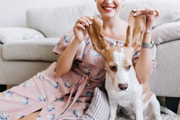 前景にかわいいビーグル犬の子犬とロマンチックなピンクのドレスで笑顔の女性の屋内の肖像画。犬の耳で遊んで笑っている白いマニキュアの素晴らしい女の子 無料写真