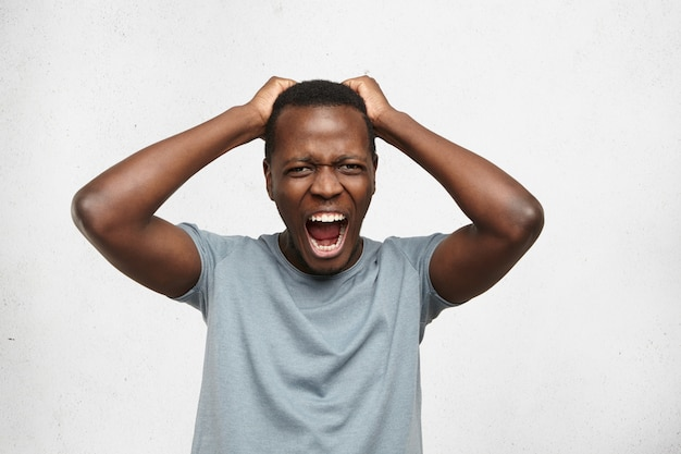 灰色のtシャツに身を包み、絶望と怒りで大声で叫ぶ、ストレスのたまったうんざりしたアフリカ系アメリカ人男性の屋内ポートレート、彼の上のアパートから来る騒音で激怒 無料写真