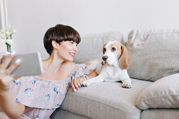 Крытый портрет чудесной темноволосой девушки, делающей селфи с собакой породы бигль, лежащей на диване Бесплатные Фотографии