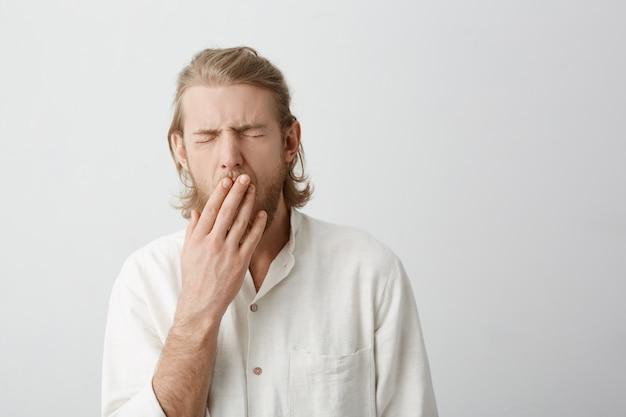 Крытый портрет молодого привлекательного белокурого мужчины зевая и прикрывая рот руками Бесплатные Фотографии