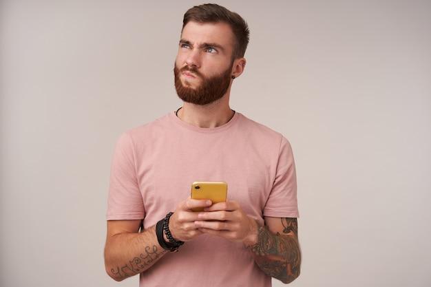 黄色のケースと思慮深く上向きに携帯電話を保持し、白で隔離のトレンディなヘアカットを持つ若い当惑した剃っていないブルネットの男性の屋内肖像画 無料写真
