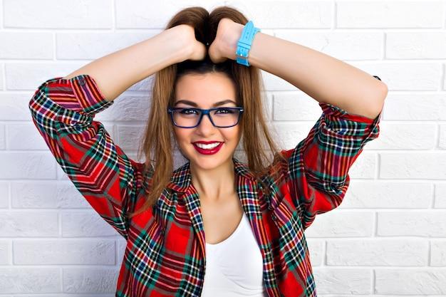 Крытый портрет молодой стильной сексуальной женщины, носящей кокетливые хвостики, сходящей с ума и веселой, улыбающейся в хипстерских прозрачных очках. Бесплатные Фотографии