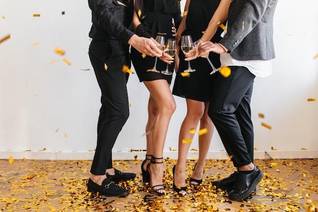 Ritratto interno di persone tintinnano bicchieri con ragazzi in abiti neri Foto Gratuite
