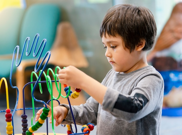 Indoor portrait preschool boy playing in kid club with vintage tone, child having fun playing colorful toys in kid playroom. kid boy playing with educational toys in kindergarten. education concept Premium Photo