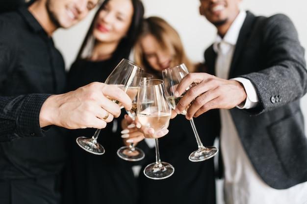 Ritratto dell'interno della donna bionda romantica agghiacciante alla festa di un amico e in posa con un bicchiere pieno di champagne Foto Gratuite
