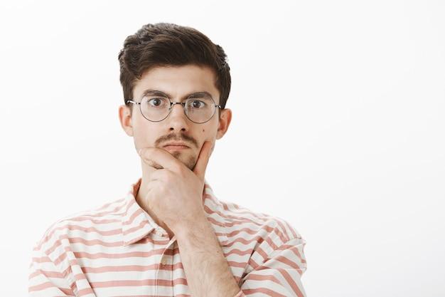 Ritratto interno di nerd maschio serio concentrato in occhiali rotondi alla moda, strofinando il mento con la mano e fissando, pensando o prendendo una decisione, risolvendo problemi matematici sul muro grigio Foto Gratuite