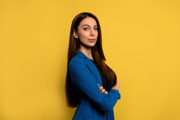 Indoor portrait of successful young woman with long dark hair wearing blue jacket posing with folded arms over yellow wall Free Photo