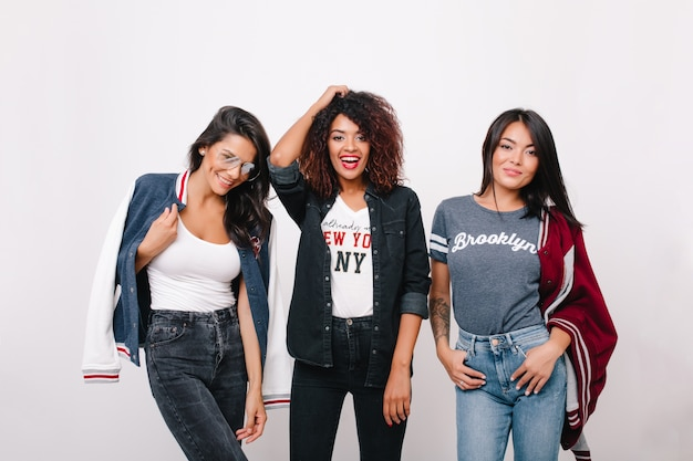 Indoor portrait of three excited female students in trendy clothes having fun together after lessons. curly girl in denim attire spending time with brunette friends and laughing. Free Photo