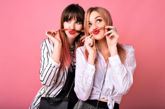Ritratto dell'interno di due donne sorelle felici migliori amici, che indossano abiti alla moda in bianco e nero e capelli rosa, abbracci e sorridenti, emozioni uscite, stile hipster Foto Gratuite