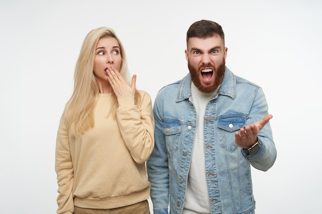 Indoor portrait of young frightened lovely blonde female looking scaredly on angry bearded handsome brunette man screaming madly, isolated on white Free Photo