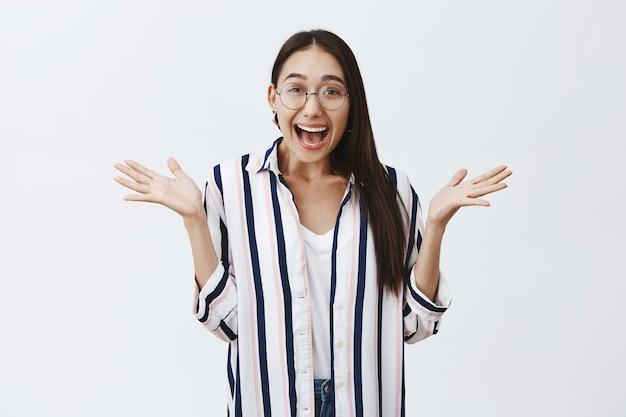 Ripresa in interni di una donna felice stupita ed elettrizzata in occhiali e camicetta a righe, che allarga i palmi per la gioia e sorride ampiamente, spiegando incredibili notizie con entusiasmo sul muro grigio Foto Gratuite
