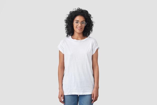 Tiro al coperto di attraente donna dalla pelle scura con capelli croccanti, indossa occhiali rotondi, vestita con una maglietta bianca casual e jeans, posa al coperto, ha un'acconciatura afro. Foto Gratuite