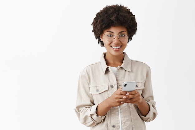 Indoor shot of attractive happy and satisfied african american woman using brand new cool smartphone and gazing pleased, smiling over gray wall Free Photo