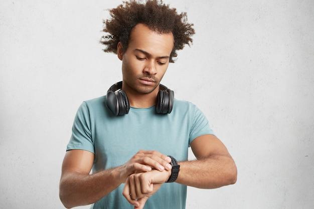 Tiro al coperto di attraente adolescente maschio con acconciatura alla moda, indossa una maglietta casual, Foto Gratuite