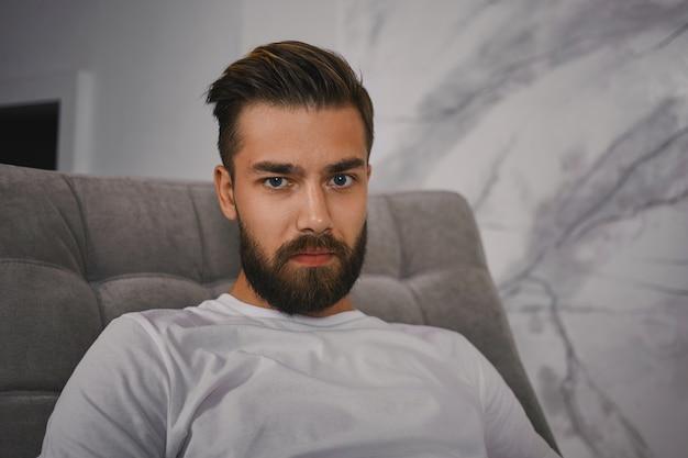 Tiro al coperto di attraente giovane maschio europeo con elegante pettinatura e barba folta fissando la telecamera con sguardo serio, seduto sul divano a casa. persone, stile di vita ed espressioni facciali umane Foto Gratuite