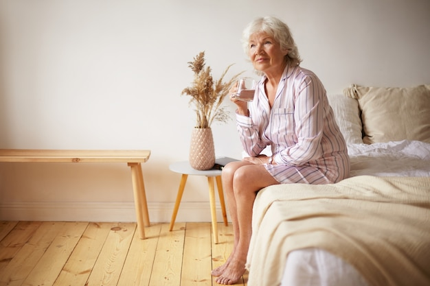 Indoor shot of barefooted attractive gray haired female pensioner sitting on bed with feet on wooden floor, holding glass, drinking fresh water in morning. people, lifestyle, bedtime and aging concept Free Photo